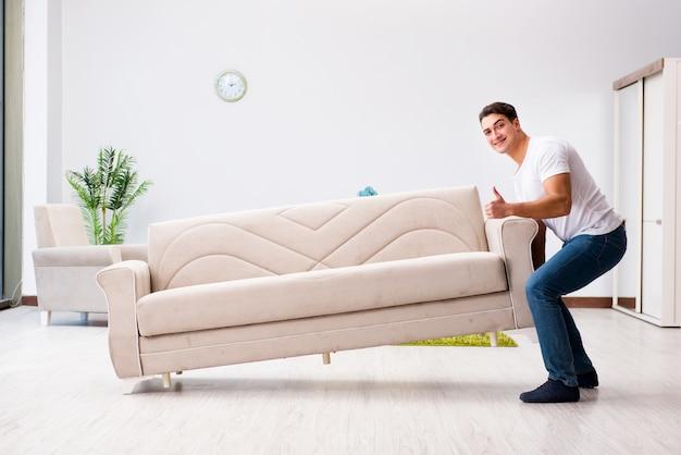 Молодой человек, перемещение мебели на дому Premium Фотографии