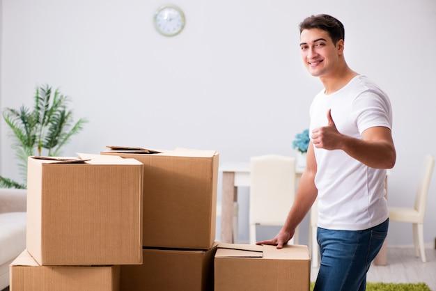 Молодой человек движется коробки дома Premium Фотографии