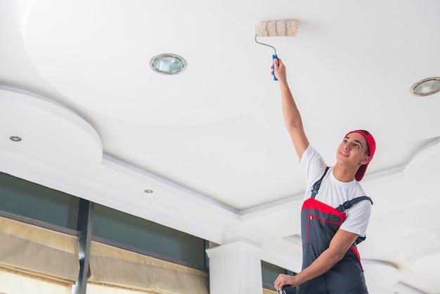 Молодой художник красит потолок в концепции конструкции Premium Фотографии