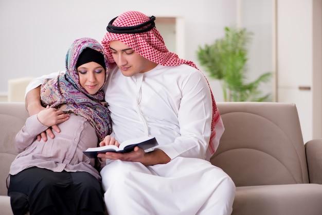 妊娠中の妻が赤ちゃんを期待して若いアラブのイスラム教徒の家族 Premium写真