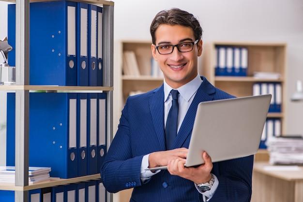 フォルダーが付いている棚の隣に立っている若い男 Premium写真