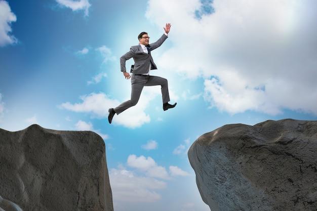 崖を飛び越える野心的な実業家 Premium写真