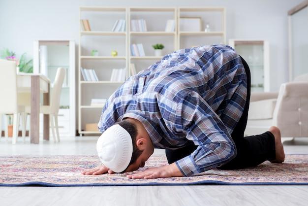 自宅で祈るイスラム教徒の男性 Premium写真