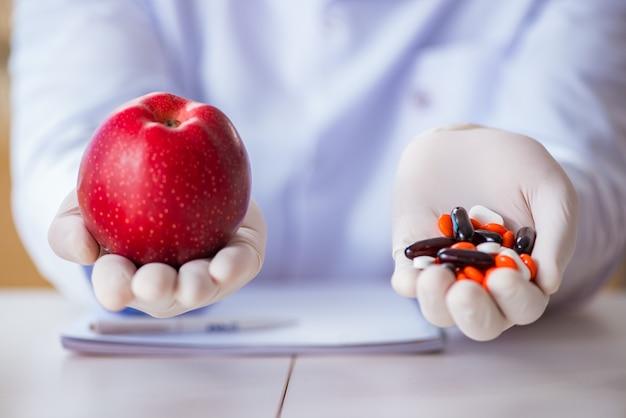 Доктор, предлагающий выбор между здоровыми и витаминами Premium Фотографии