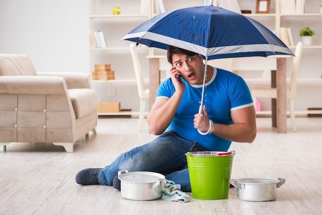 Человек дома имеет дело с утечкой наводнения соседа Premium Фотографии