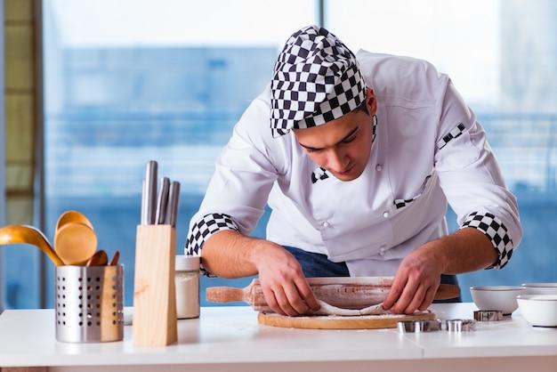 若い男が台所でクッキーを調理 Premium写真