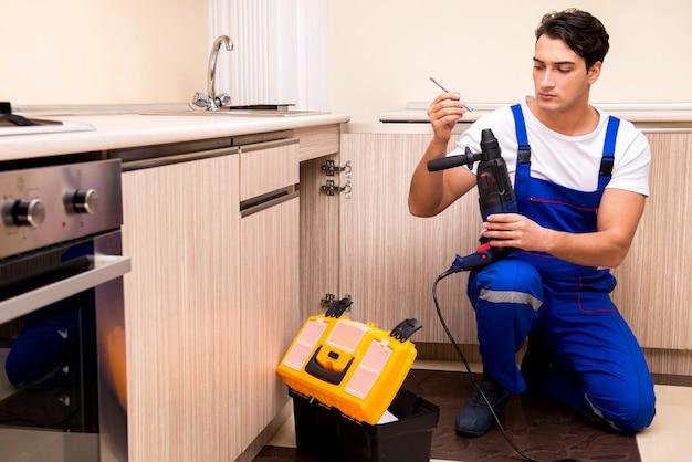 キッチンで働く若い修理工 Premium写真