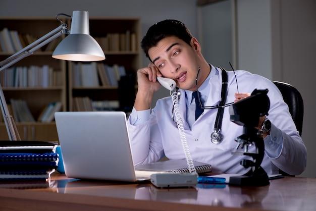 オフィスで遅くまで働く若い医者 Premium写真