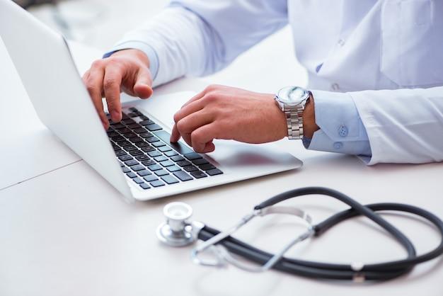 Доктор работает на компьютере Premium Фотографии