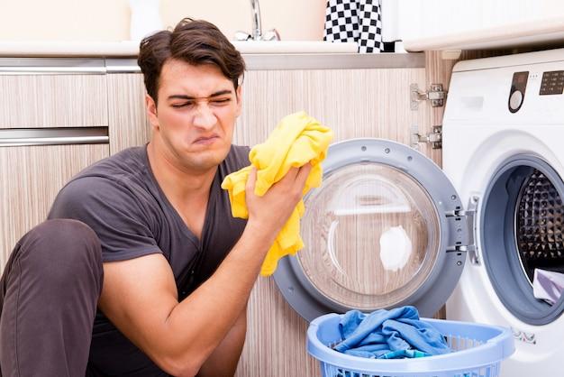自宅で洗濯をしている若い夫男 Premium写真