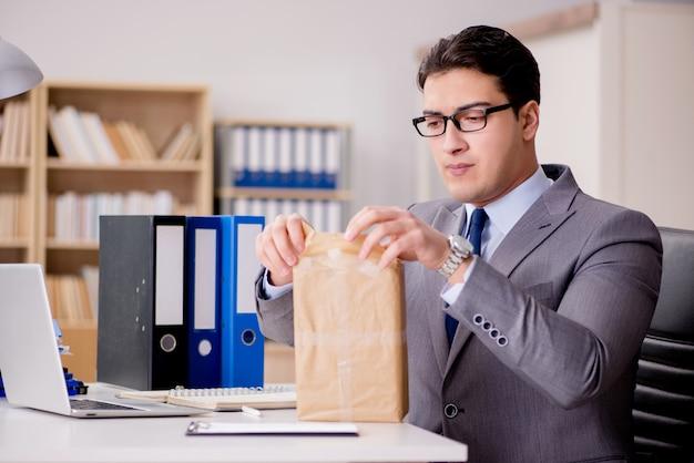 オフィスで小包を受け取るビジネスマン Premium写真