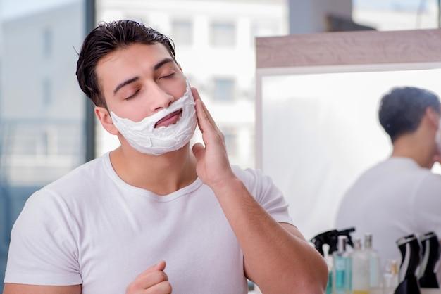 Молодой красавец бритья утром Premium Фотографии