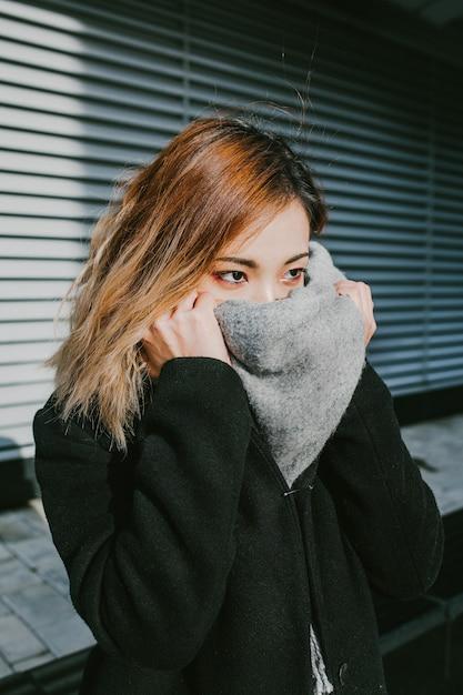 アジアの女の子の外観はスカーフの顔を閉じます Premium写真