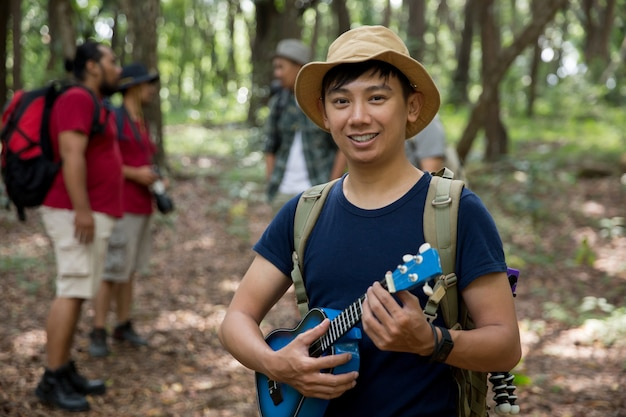 Мужчина с гавайской гитарой, поход в лес Premium Фотографии