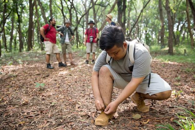Человек турист, связывая его обувь Premium Фотографии