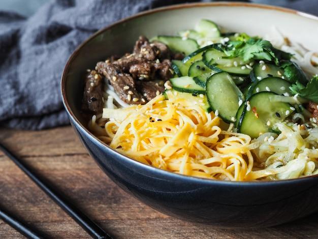 野菜、スクランブルエッグ、牛肉と麺をボウルに入れて箸で冷やした韓国のククシスープ Premium写真