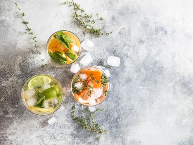 灰色の背景にガラスの異なる柑橘類と夏の冷たい飲み物を設定します。 Premium写真