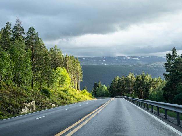 二重の黄色の線で空のアスファルト道路の眺め。 Premium写真