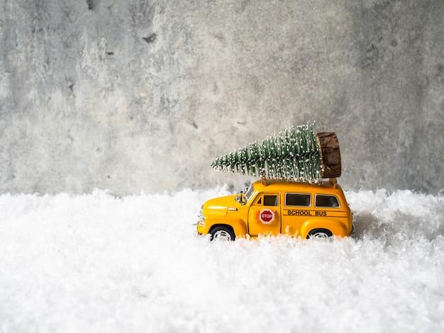 小さな黄色のおもちゃのスクールバスは屋根の上にクリスマスツリーを運ぶ Premium写真