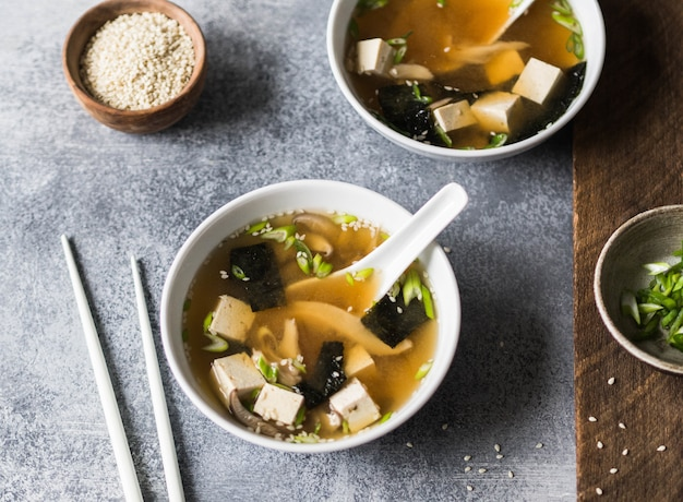 灰色と木の背景にスプーンと白の箸で白いボールにオイスターマッシュルームと日本の味噌汁。 Premium写真