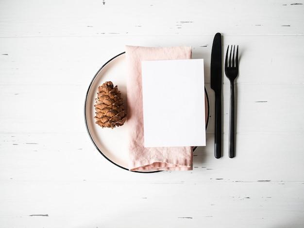 Деревенский стол с рождественские настройки с пластиной, розовые салфетки, меню карты и приборы на белый деревянный стол. вид сверху. Premium Фотографии