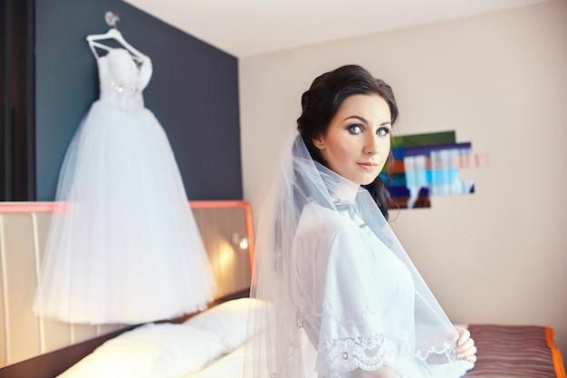 バスローブで部屋の女性はウェディングドレスを立っています。 Premium写真