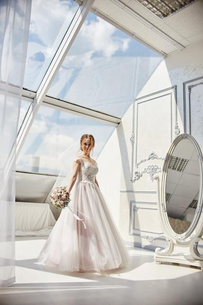 新郎を待っているウェディングドレスの朝の花嫁女性 Premium写真
