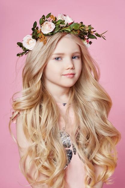 頭の上の花の花輪。笑顔のモデルのポーズの女の子 Premium写真