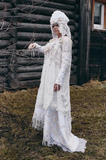 女の子の新しい民族のロシアのファッション流行の創造的な服は古い家、白いドレスと帽子に近いポーズします。 Premium写真