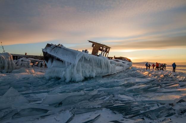 日没時のバイカル湖、すべてが氷と雪で覆われ、厚い澄んだ青い氷 Premium写真