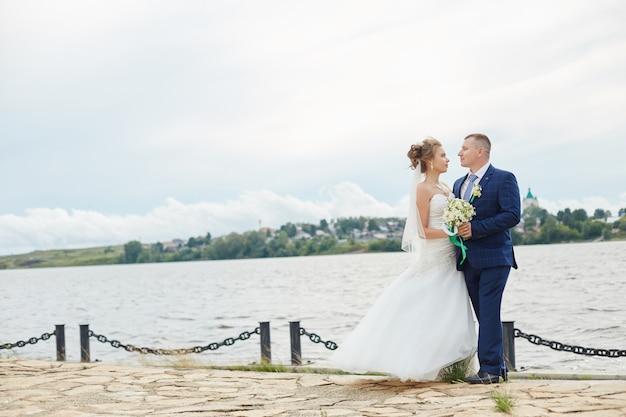 カップルが抱きしめて水の近くの家にキス Premium写真