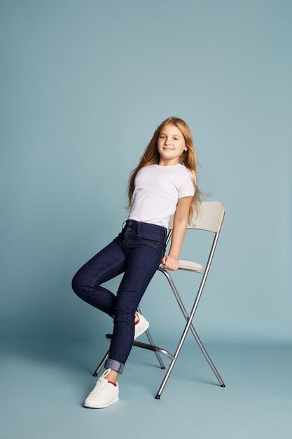 椅子に座って長い髪の美しい少女 Premium写真