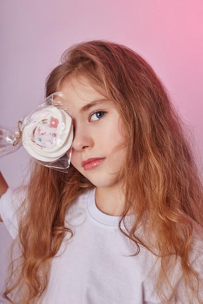 ブロンドの髪を持つ美しい少女は、ロリポップ、手でスティックに丸いキャラメルを食べる Premium写真