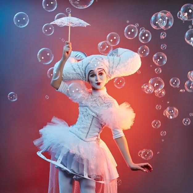 サーカスのパフォーマーのマジシャンがシャボン玉でトリックを披露します。女性と少女は、サーカスショーでシャボン玉を膨らませる Premium写真