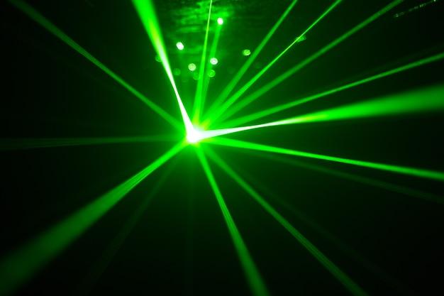 ナイトクラブの緑と赤のレーザー。暗い背景、クラブの雰囲気のレーザービーム Premium写真