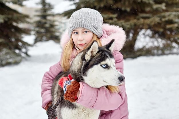 子供たちは雪の中で座り、犬のハスキーをなでます。冬に子供たちが外に出てハスキー犬と遊ぶ Premium写真