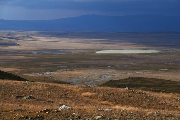 白い積雲の雲が山から降りてくる、草原の秋の風景 Premium写真
