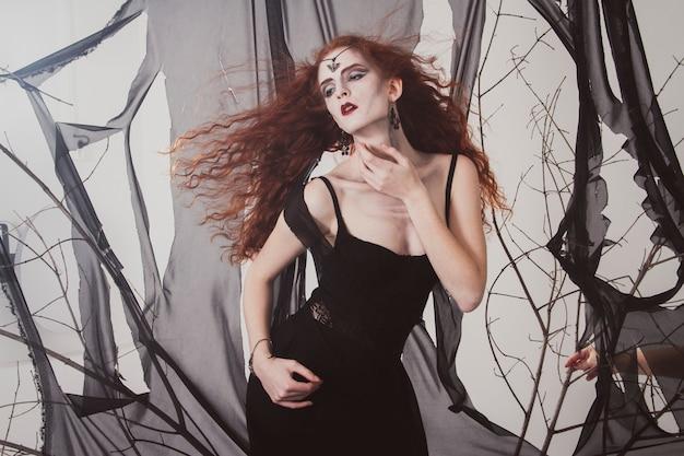 魔女がハロウィーンを待っている赤毛の女性。赤髪の女性の黒魔道士。神秘的な魔術、魔法の魅力 Premium写真