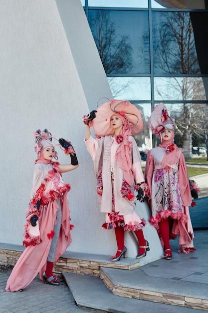 新しいファッションの女の子、ストリートでポーズをとる流行の創造的な服、ピンクのドレスと帽子、民族服 Premium写真