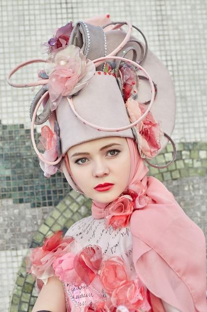 女の子の新しいファッション流行の創造的な服は屋外でポーズ、ピンクのドレスと帽子 Premium写真