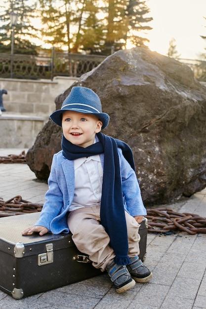 スーツケースを持つ子供旅行、レトロな秋の春服。 Premium写真