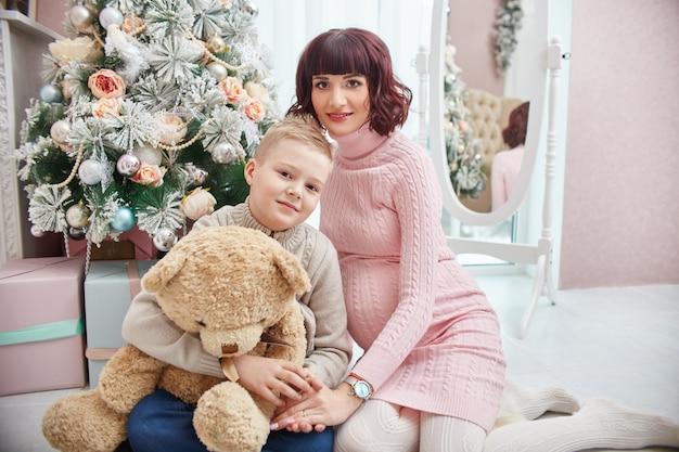 クリスマスツリーの横にポーズの息子と妊娠中の母親 Premium写真