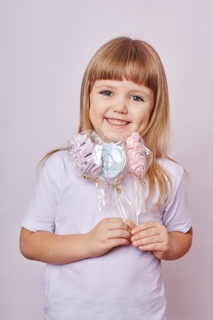 Красивая девушка со светлыми волосами ест леденец, круглая карамель на палочке в руках веселой улыбающейся девушки. девочка с длинными волосами в белой футболке лижет леденец. Premium Фотографии