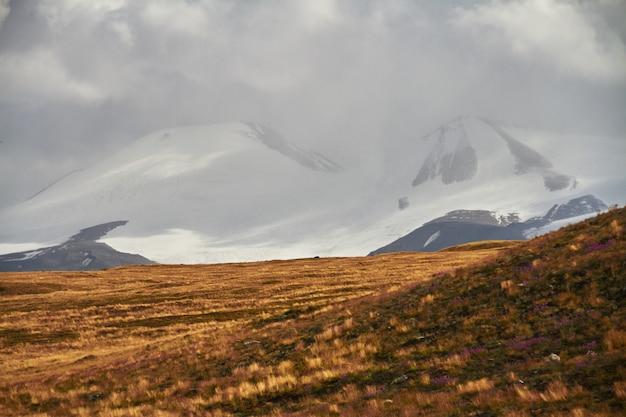 白い積雲の雲が山から降りてくる、草原の秋の風景。アルタイのウコク高原。素晴らしい寒い風景。誰でも Premium写真