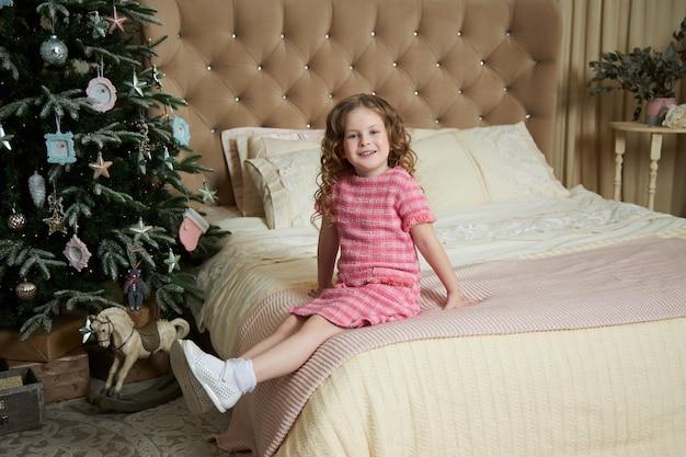 少女とクリスマスの朝、クリスマスツリーのインテリアを背景にポーズをとる子 Premium写真