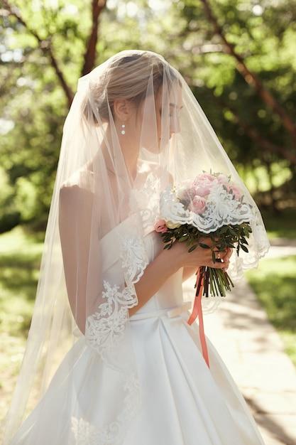 Свадебный портрет женщины невесты под белой вуалью. Premium Фотографии