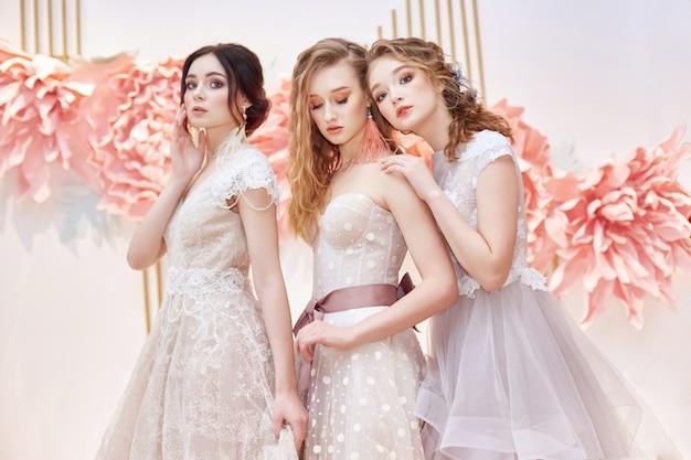 高価なウェディングドレスの美しいトリオ花嫁 Premium写真