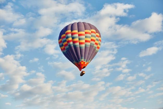 Воздушный шар летать утром в небе в лучах рассветного солнца Premium Фотографии