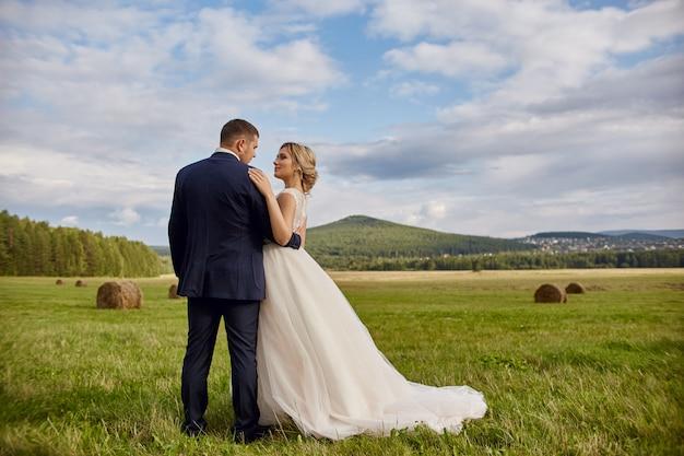 新婚夫婦は、フィールドで、結婚式を歩いてリラックス Premium写真