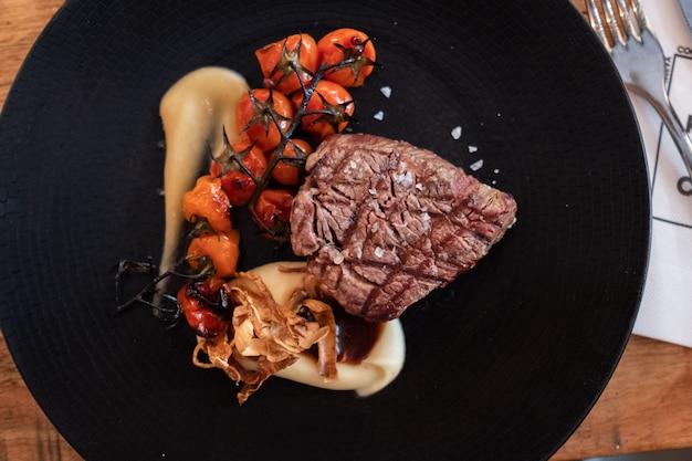 牛ヒレ肉の素朴なマッシュポテト、ローストチェリー、コンフィのガーリックソースのダークプレート Premium写真